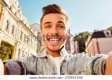 Cheerful happy man making comic selfie on the street - stock photo
