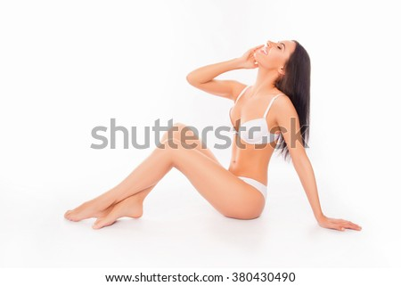 Cheerful happy model in white underlinen touching her face - stock photo