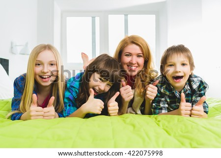 cheerful happy mother with children lying on the bed and showing thumbs up - stock photo