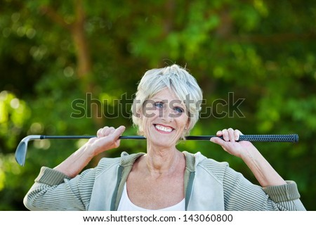 Cheerful happy older woman with a golf stick in the golf club. - stock photo