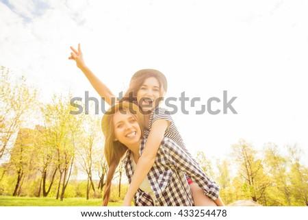 Cheerful happy woman piggybacking her pretty girlfriend - stock photo
