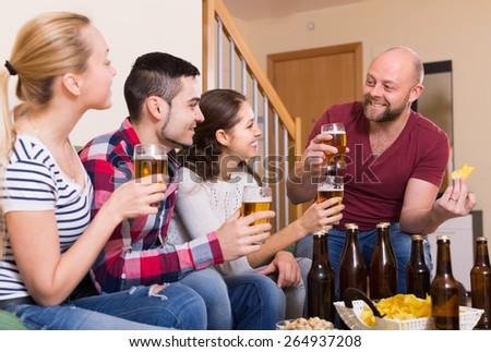 Cheerful happy young adults drinking beer and laughing indoor. Selective focus - stock photo