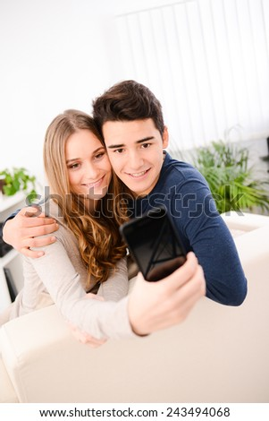 cheerful happy young couple making selfie together at home - stock photo