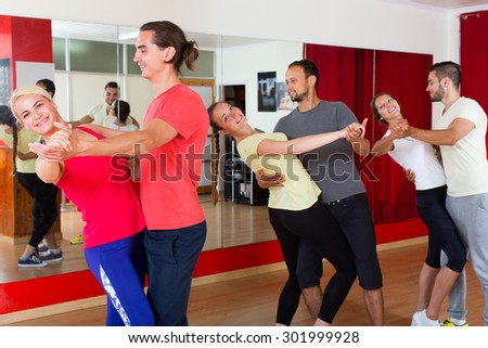 Cheerful happy young couples dancing pair dance in studio. Selective focus