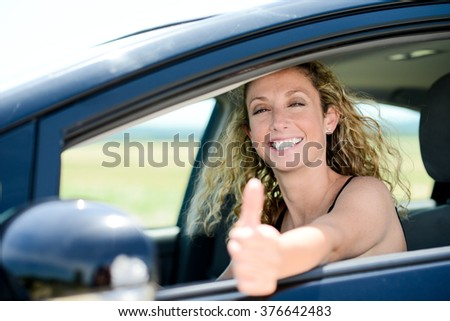 cheerful happy young woman driving her new car