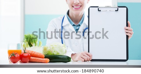 Cheerful healthcare professional promoting healthy eating - stock photo