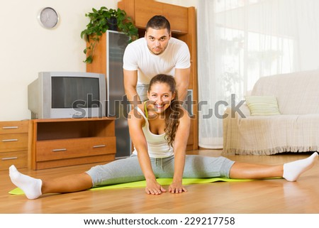 Cheerful healthy couple doing fitness on the mat - stock photo