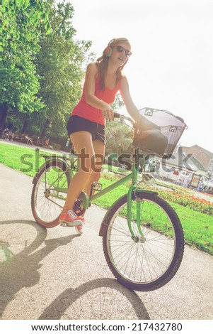 Cheerful Hipster Girl Riding Bike In The Park - stock photo