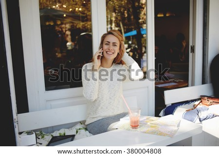 Cheerful hipster girl talking on mobile phone while enjoying rest in comfortable sidewalk restaurant, smiling European female having pleasant conversation on cell telephone during lunch in cozy cafe - stock photo