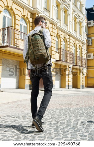 Cheerful hipster guy is walking with backpack on his shoulder.  Focus on his back - stock photo
