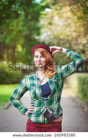 Cheerful hipster redhead girl in hat with retro camera outdoor