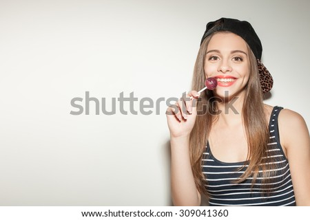 Cheerful hipster woman is eating lollipop with joy. She is touching it to her lips and smiling. The woman is wearing cap. Isolated and copy space in left side - stock photo