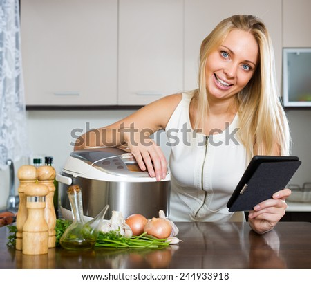 cheerful housewife reading ereader and cooking with multicooker at home interior - stock photo