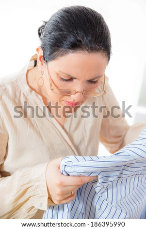 Cheerful housewife standing at the ironing board and looks at the laundry that needs to iron - stock photo