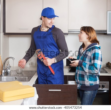 cheerful housewife watching as worker repairing  water lines