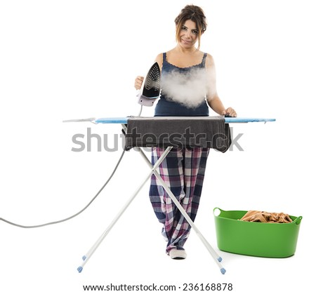 Cheerful housewife with a beautiful smile standing at the ironing board ironing clothes . - stock photo
