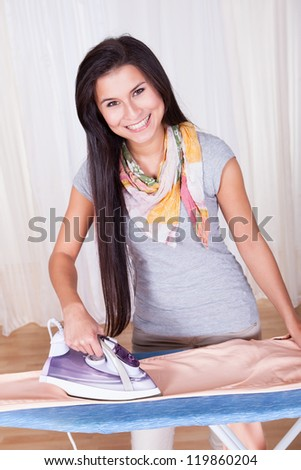 Cheerful housewife with a beautiful smile standing at the ironing board ironing clothes against a white curtained window with copyspace - stock photo