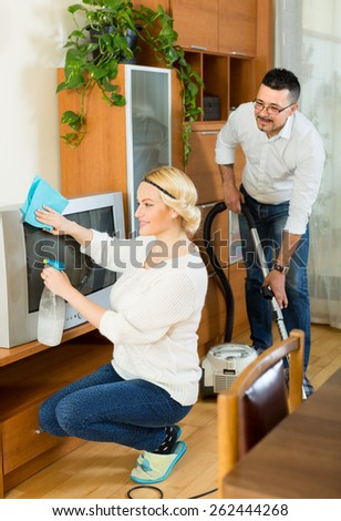 Cheerful husband helping his young wife cleaning the room. Focus on woman - stock photo
