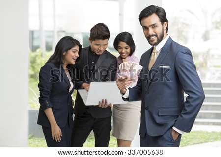 Cheerful Indian businessman holding rupees with his busy colleagues on white background. - stock photo