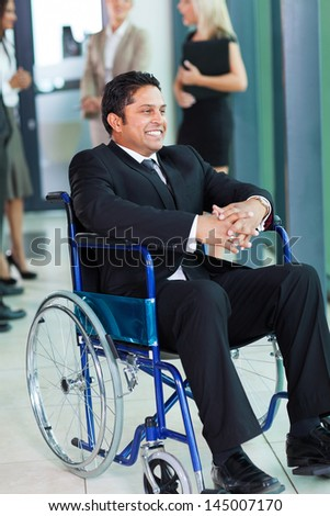 cheerful indian businessman in wheelchair with colleagues on background - stock photo