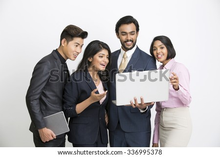 Cheerful Indian businessman standing with his team on white background. - stock photo