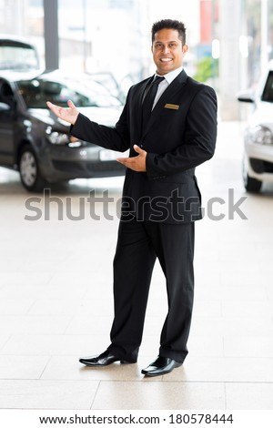 cheerful indian car salesman doing welcoming gesture - stock photo