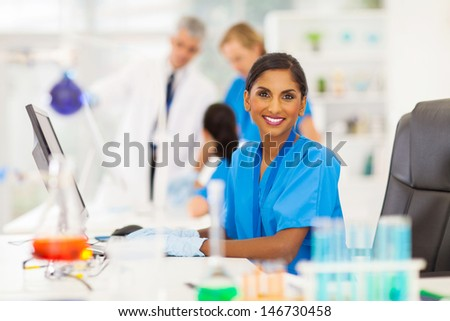 cheerful indian laboratory worker using computer in lab - stock photo