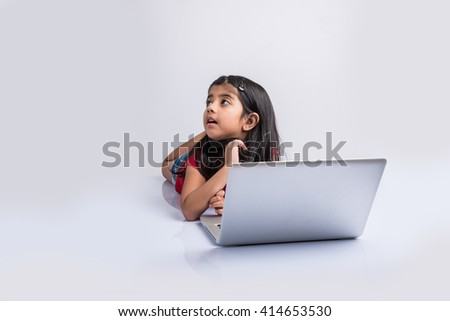 cheerful indian little girl using laptop, asian small girl playing on laptop, isolated over white background, cute indian baby girl lying on floor playing on laptop - stock photo
