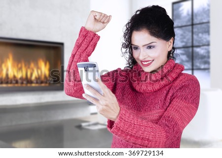 Cheerful indian woman wearing sweater at home and rise hand while reading message on the cellphone, shot at wintertime - stock photo
