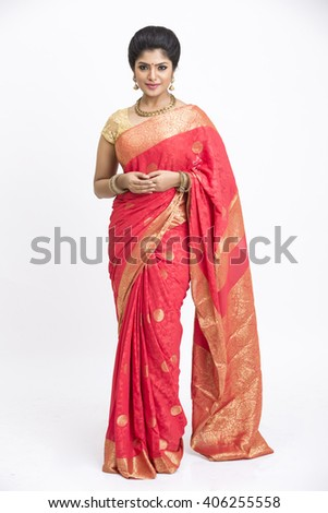 Cheerful indian young girl posing in traditional Indian saree on white background