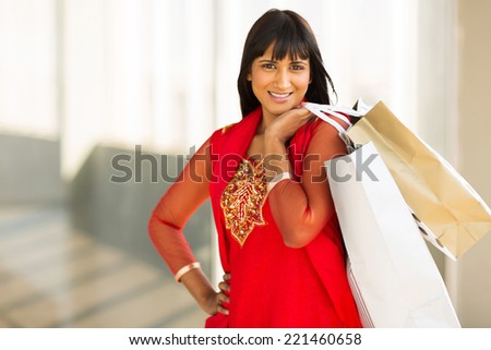 cheerful indian young lady shopping in mall - stock photo