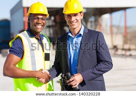 cheerful industrial manager and worker outdoors - stock photo
