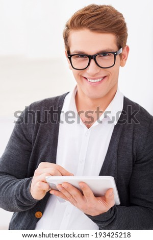 Cheerful IT guy. Handsome young man working on digital tablet and smiling while standing indoors - stock photo