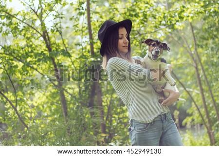Cheerful Jack Russell Terrier's puppy barks joyous in arms of sweet young stylish girl in natural environment in springtime - stock photo