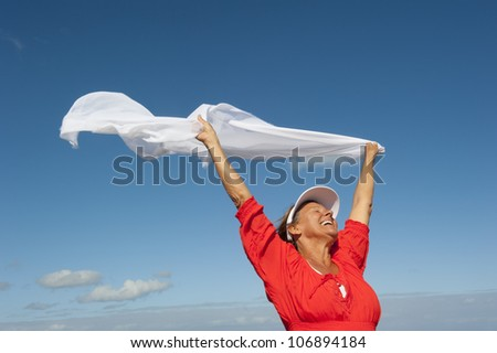 Cheerful, joyful, happy mature woman holding white fluttering cloth in the wind, isolated with blue sky as background and copy space. - stock photo