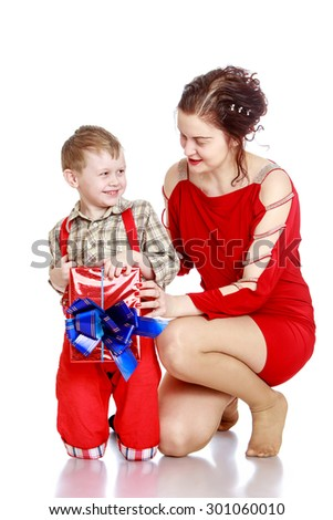 Cheerful, joyful little boy in a plaid shirt and long red shorts holding a beautifully wrapped box decorated with a bow. In the box is a gift that he gave his beloved mother. Together with my mother - stock photo
