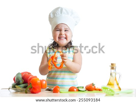 cheerful kid girl preparing healthy food in the kitchen