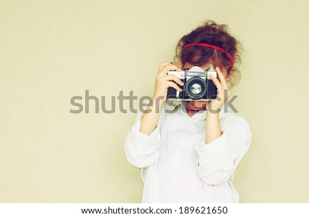 Cheerful kid holding old camera. retro filter room for text. - stock photo