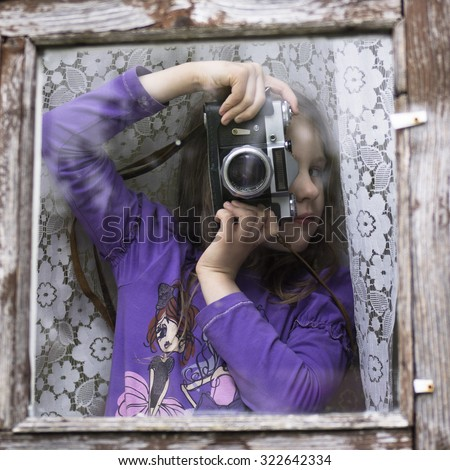 Cheerful kid holding old retro camera in the wooden framed window - stock photo