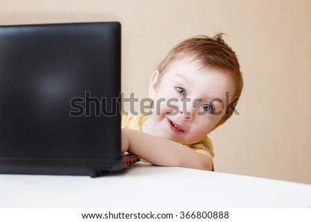 cheerful kid peeks out from behind his laptop. cute little boy is working and playing on the computer. computer buff. look at the camera