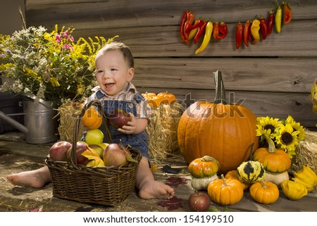 Cheerful kid with a pumpkin and apple on the background of wooden wall