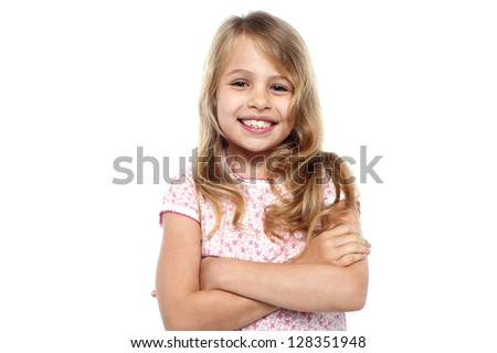 Cheerful kid with folded arms flashing a warm smile.