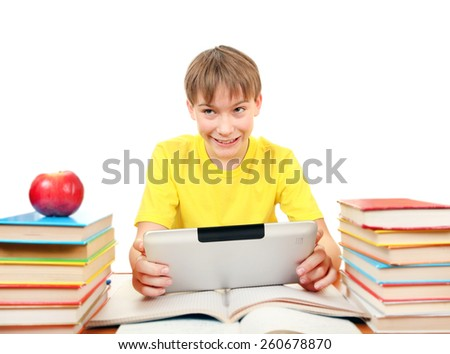 Cheerful Kid with Tablet Computer at the Desk with the Books on the White Background
