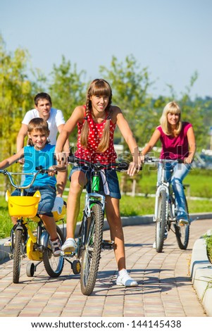 Cheerful kids and their parents riding bikes - stock photo