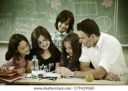 Cheerful kids at school room having education activity - stock photo