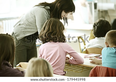 Cheerful kids at school room having education activity with teacher - stock photo