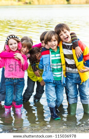 Cheerful kids group in rubber boots - stock photo