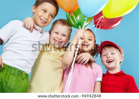 Cheerful kids holding a bunch of colorful balloons - stock photo