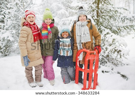 Cheerful kids in snowfall looking at camera in winter park - stock photo