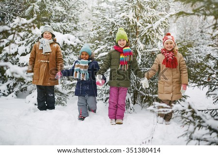 Cheerful kids in winter-wear looking at camera on background of fir-trees - stock photo